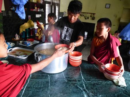 Essensausgabe durch den Koch und ältere Schüler
