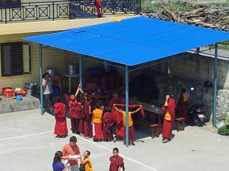 Unter dem Vordach wird gemeinsam gegessen ( Principal, Lehrer und Volonteers)