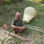 Alter Mann bearbeitet mit der Sichel einen Bambus für einen Tragekorb